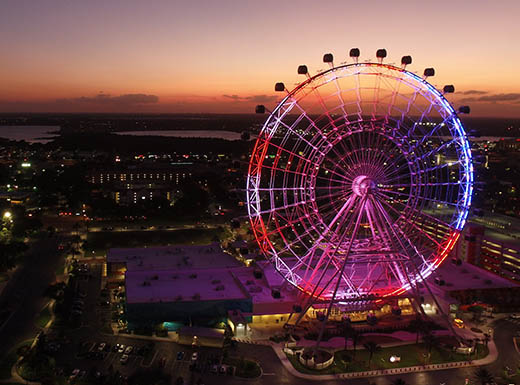 Aeiral view of Orlando, Florida, at dusk, featuring a large Ferris wheel