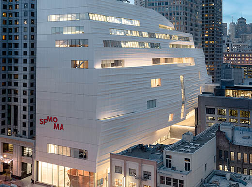 Exterior view of the San Francisco Museum of Modern Art, aka SFMOMA, lit up on a clear evening night