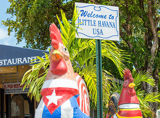 welcome to little Havana sign between chicken statues wearing American and Cuban flags