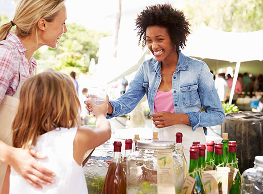 A smiling woman passes a drink to a happy young girl with her mother at a table outside in Orlando, Florida