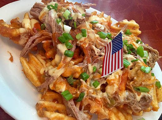 Delicious white plate of food with melting cheese, French fries and green onions, and a small American flag stuck in the middle, at San Francisco restaurant