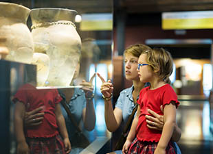 A blonde mother and daughter look at pieces of art in the window of a museum in Orlando, Florida""