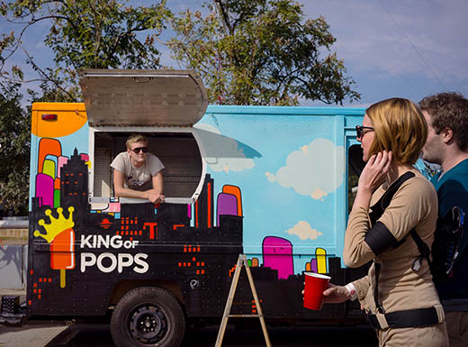 Onlookers check out King of pops food truck on a sunny day in Atlanta, Georgia