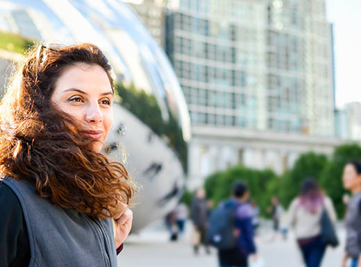 Female tourist standing outside in Millenium Park in front of The Bean smiling in Chicago during daytime