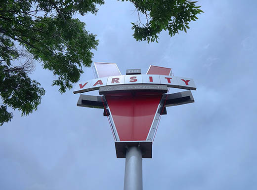 The Original Varsity Sign next to tree on cloudy day in Atlanta, Georgia