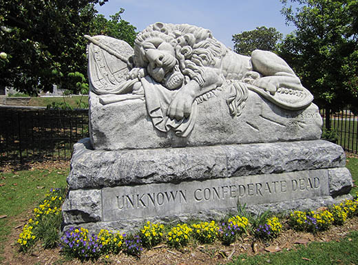 Large headstone featuring a lion at Oakland Cemetery in Atlanta, Georgia, on a sunny day
