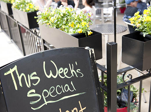 Exterior shot of a restaurant patio with silver tables and yellow and green plants; with a weekly special sidewalk sign outside the black gate