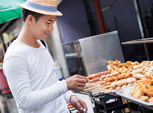 A young man enjoying a taste of Thai food from a street vendor in Denver, Colorado