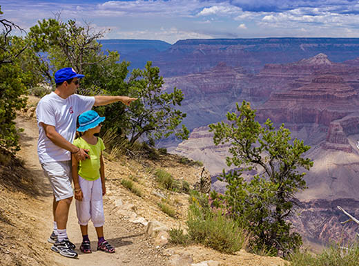 "=""Father and daughter walk along path overlooking grand canyon"