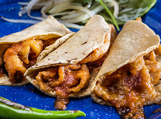 Three mouthwatering Tacos de Chicharron resting on a blue plate at a Miami restaurant