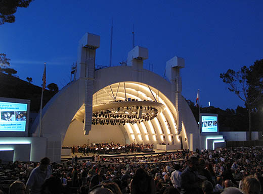An orchestra playing live music in front of a packed house at the Hollywood Bowl in Los Angeles, CA