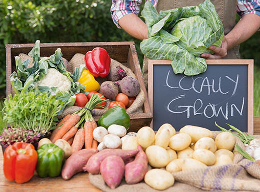 Red and green peppers, sweet potatoes, carrots, potatoes and cauliflower displayed on a wooden table with a chalkboard sign that has Locally Grown written on it in chalk, as a person holds a head of lettuce in the background