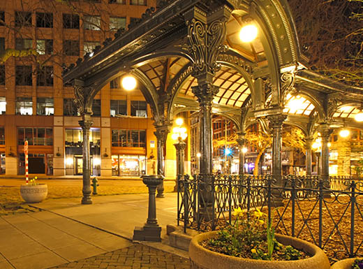 The stunning Romanesque Revival architecture is one of many attractions in Pioneer Square in Seattle, Washington; pictured at night, lit up by street lights