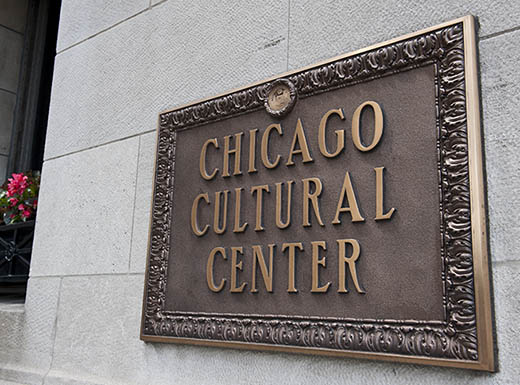 sign for the Chicago Cultural Center on the outside marble wall of the building, next to the entry with flowers in the background