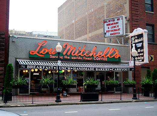 Exterior shot of the front of Lou Mitchell's restaurant  with the red sign illuminated  in Chicago, Illinois