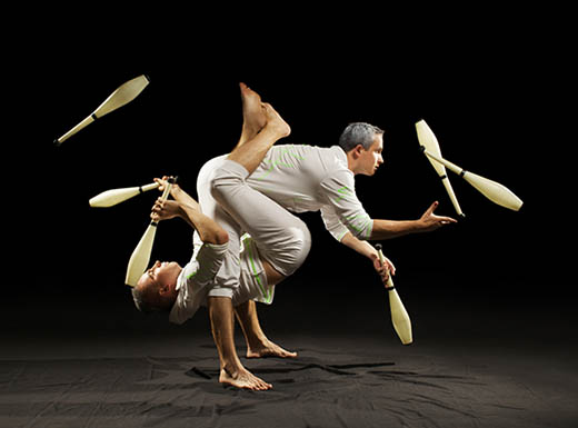 Two performers juggle bowling pins while performing acrobatics together in Las Vegas, Nevada""