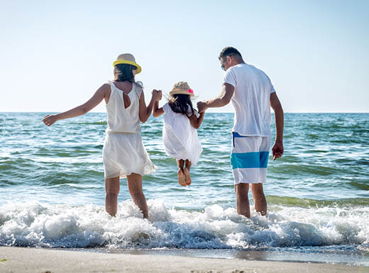 Mother, father and child playing in the surf on a Fort Lauderdale beac
