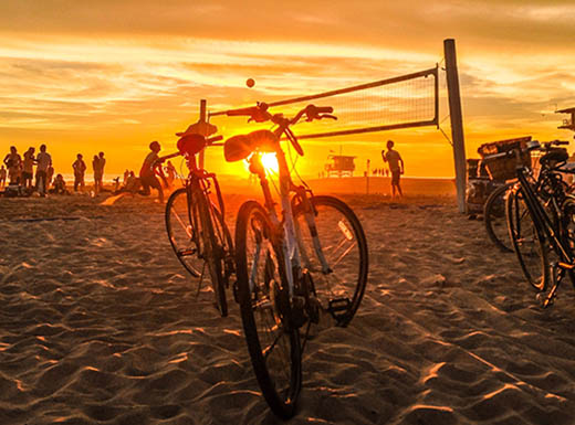 Bicycle's parked in the sand near a beach volleyball net where people are playing a game at sunset on Venice Beach in Los Angeles