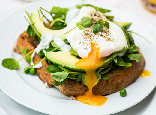 A poached egg sits on top of a piece of whole wheat toast topped with spinach and avocado on a white plate on a white tablecloth on a table in a restaurant in Phoenix, Arizona