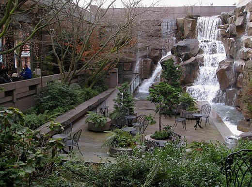 Buildings surround a tall waterfall in Waterfall Garden, located in Seattle's Pioneer Square