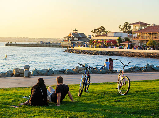 Couple sitting on grass next to bikes watch the sun set at Cliffs Natural Park in San Diego, CA