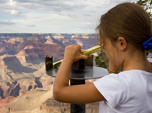 Young girl looks through binoculars over the grand canyon
