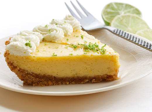 A delicious slice of key lime pie is served on a plate with a fork in Miami
