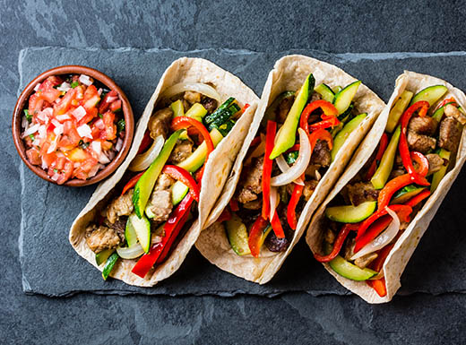Three tacos sit lined up topped with chicken and chopped up red peppers and zucchini with a side of fresh salsa on a slate serving board on a slate table in a restaurant in Phoenix, Arizona