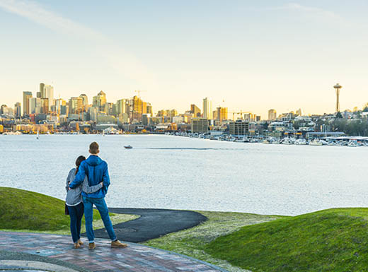 A young couple stands in front of a body of water with the Seattle skyline in the background