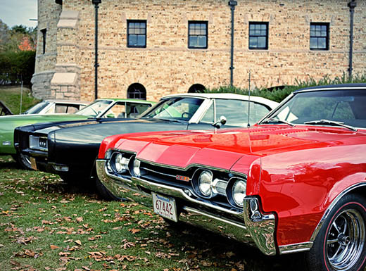 4 old muscle cars lined up outside on grass in front of building