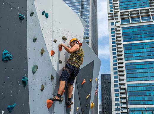 Man climbing an artificial rock wall in Maggie Daley Park in Chicago