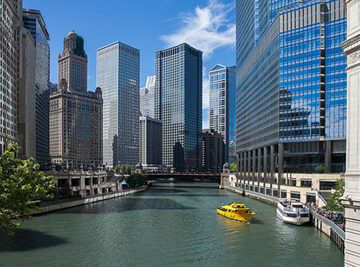 View of boats in Chicago River amidst tall buildings