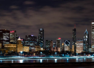 View of the Downtown Chicago skyline well-lit at night with clouds in the background against a black sky