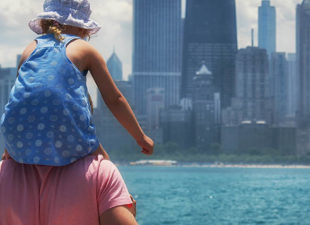 Little girl on the shoulders of her father in Chicago along the water
