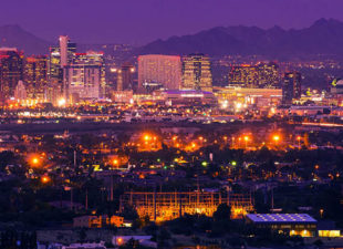 The skyline of Phoenix, Arizona is seen at night with the city lights on and a big full moon over the Arizona mountains in the background