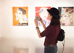A young woman in a red shirt, grey jeans and black hat holds a camera inside an art gallery in Las Vegas, Nevada