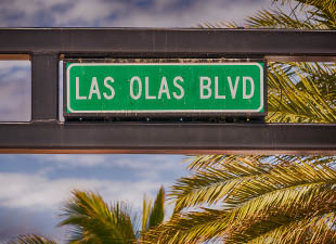 Las Olas Boulevard street sign in front of palm trees in Fort Lauderdale, Florida
