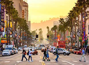 Traffic and pedestrians on Hollywood Boulevard at dusk