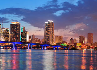 Sun sets in the background during a panorama view of Miami's downtown city landscape taken from the water