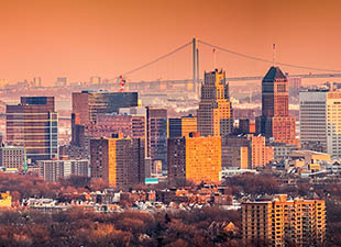 Panoramic view of Newark, New Jersey, skyline under an orange sunset