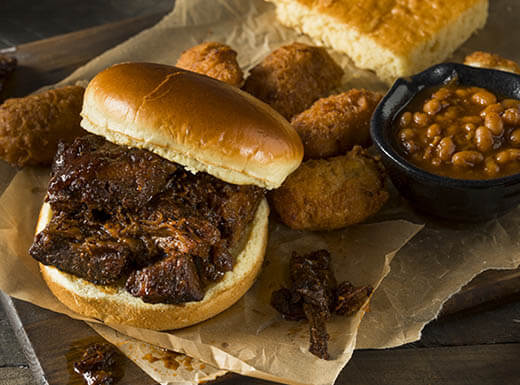 A slow smoked brisket sandwich is pictured with a bowl of baked beans and cornbread on a platter during daytime in a Houston, Texas resetaurant.