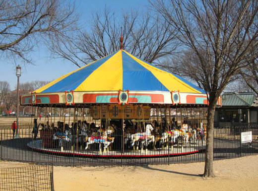 A yellow and blue topped carousel is pictured surrounded by trees with no leaves at National Mall in Washington, D.C.