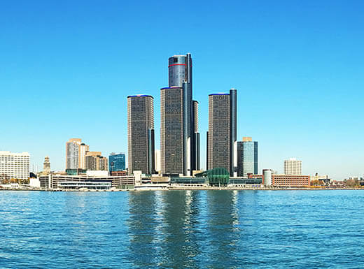 A panorama view of the Detroit, Michigan skyline from the Riverfront Trail on a bright sunny day shows and a bright blue sky and  skyscrapers