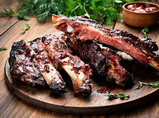 A wooden platter of roasted sliced BBQ pork ribs is pictured on a table with a big bunch of cilantro in the background during daytime in a restaurant in Houston, Texas.