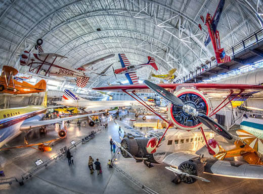 Red, white, and blue aircraft sit on display inside a large domed building at The National Air and Space Museum in Washington, D.C.