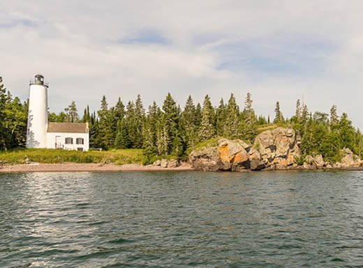 View from the ocean looking back at land with Rock Harbor Lighthouse surrounded by pine trees under a gray sky on Isle Royale National Park, Michigan.
