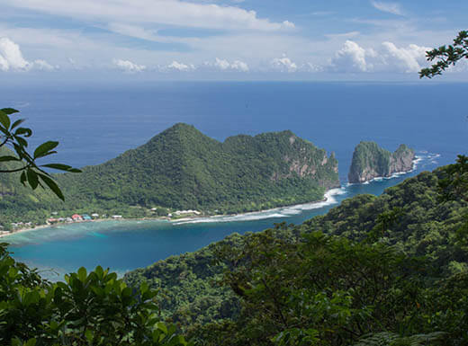 Looking over dense rainforests at a bay of beautiful blue water on Pola Island in the National Park of American Samoa.