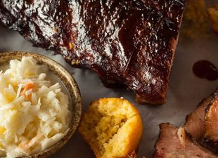 A white platter of BBQ smoked brisket and ribs with corn, corn bread and coleslaw sits on a table during daytime in a restaurant in Houston, Texas