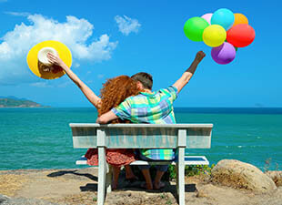 A couple sits beachside on a bench with balloons as they take in the coastal view on a sunny afternoon.