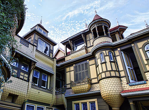 The classic-looking exterior of the Winchester Mystery House in San Jose, California is pictured from below, with a light blue sky in the background